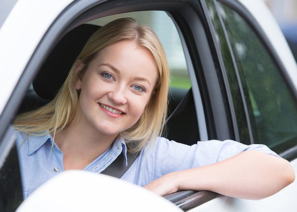 Young lady smiling out window of car - Auto Insurance