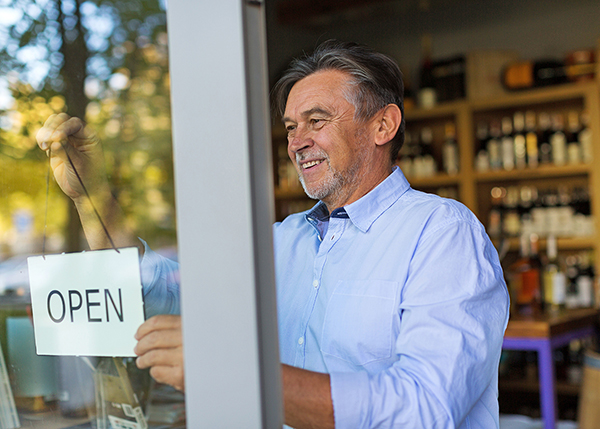 Man smiling while putting up open sign - Business Insurance