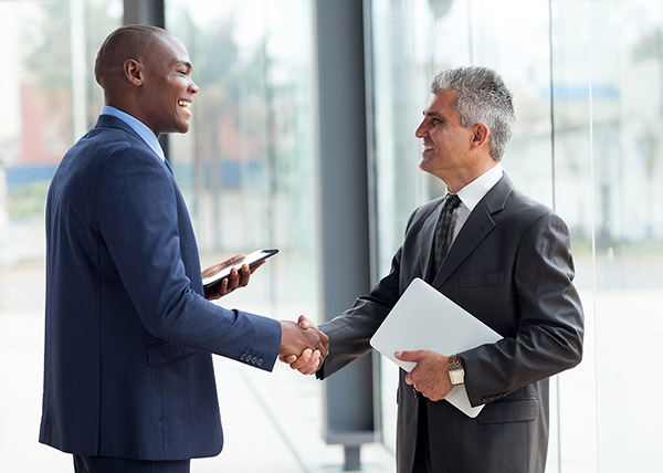 Two men shaking hands after discussing Errors & Omissions